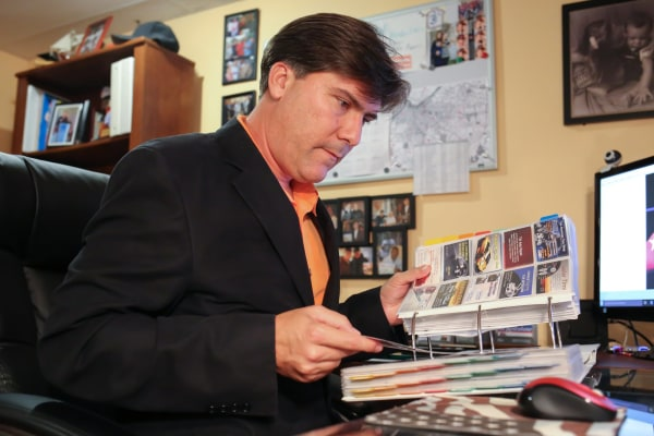 Luis Fuentes looks through business cards featuring companies run by Cubans.