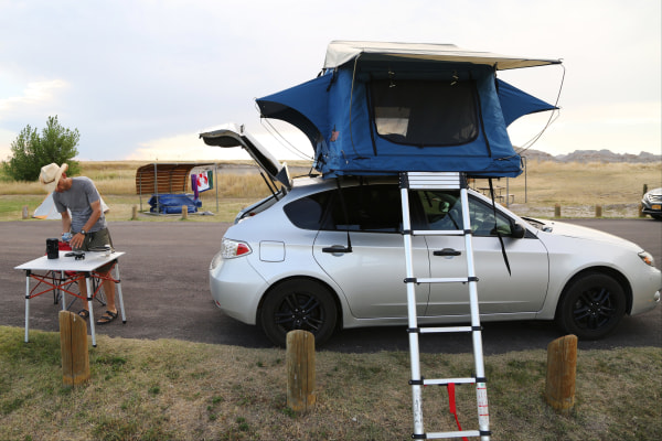 Image: Bill Sycalik gets ready to make dinner at a campsite in Badlands National Park