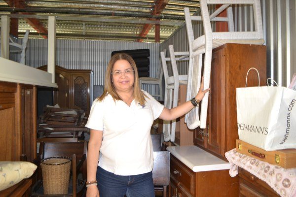 Patricia Andrade shows furniture in one of the storage spaces for Raices Venezolanas or Venezuelan Roots