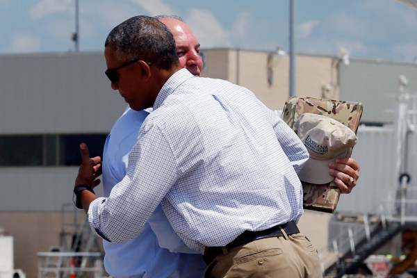 Image: U.S. President Barack Obama embraces Louisiana Governor John Bel Edwards as he arrives aboard Air Force One at Baton Rouge Metropolitan Airport in Baton Rouge