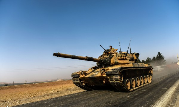 Image: A Turkish army tank drives towards Syria in the Turkish border city of Karkamis