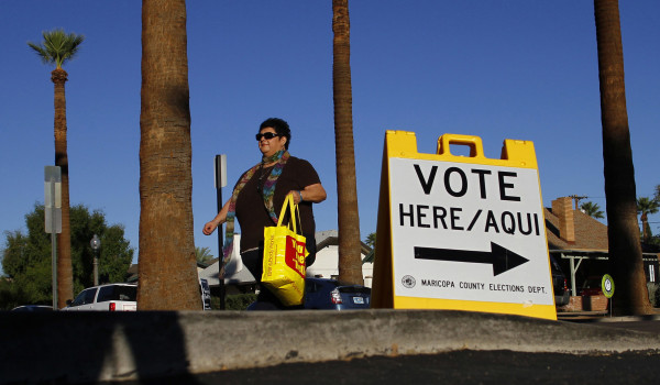 A woman walks past a sign directing voters to a polling place in the Phoenix