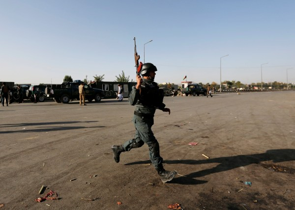 Image: An Afghan policeman arrives at the site of a suicide attack in Kabul