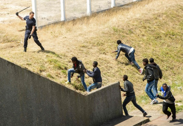 Image: French anti-riot police try to prevent illegal migrants in Calais, France