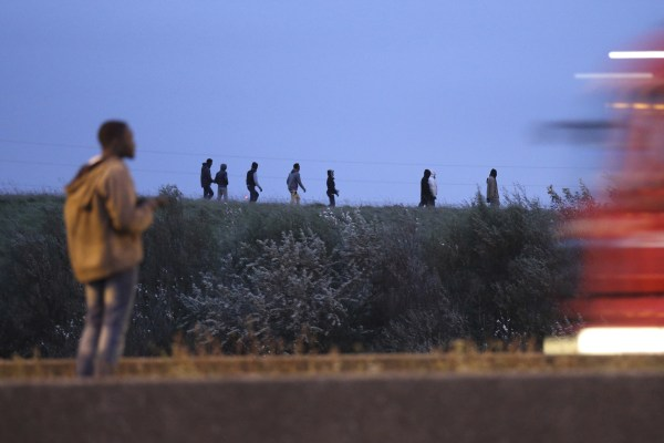Image: Migrants walk on a ridge above a road in Calais, France
