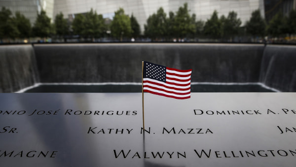 Image: An American flag is seen in the plaque of names on the edge of the South Pool of the 9/11 Memorial  in New York