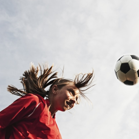 Young soccer player bouncing ball off head