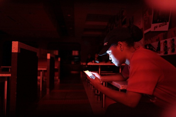 Image: An employee at a fast-food restaurant in a shopping mall uses her mobile phone during a power outage that affected several areas in the country, in San Juan