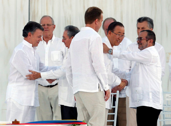 Image: Colombia's President Santos and Cuba's President Castro shake hands as UN Secretary-General Ban Ki-moon and Marxist rebel leader Londono shake hands as well in Cartagena