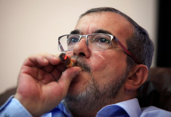 Image: FARC rebel leader Rodrigo Londono smokes a Cohiba cigar while watching a live transmission of the referendum on a peace deal, in Havana, Cuba