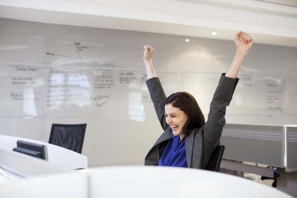 Enthusiastic businesswoman with arms raised in office
