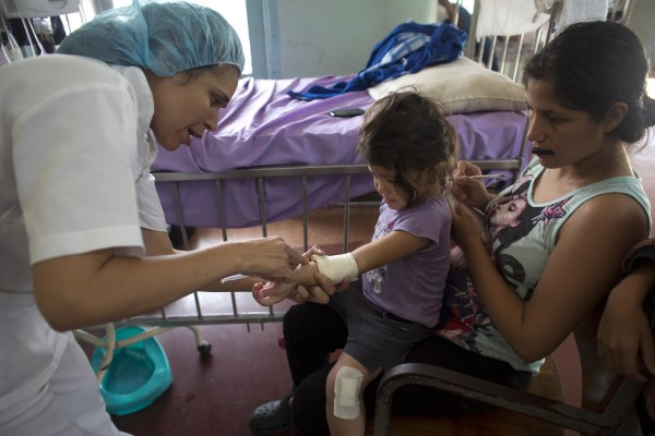 Oriana Pacheo watches intently as a nurse injects antibiotics into the arm of her 3-year-old daughter Ashley, at University Hospital in Caracas, Venezuela.