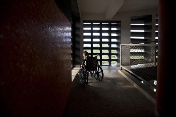 In this Sept. 19, 2016 photo, Marvin Osuna sits near a sunlit window in a passageway at University Hospital, in Caracas, Venezuela.
