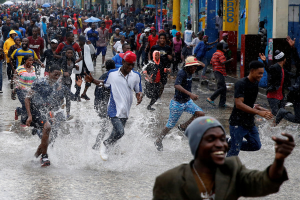 Image: Supporters of Fanmi Lavalas political party splash around in water on a flooded street as they take part in a gathering while Hurricane Matthew passes in Port-au-Prince