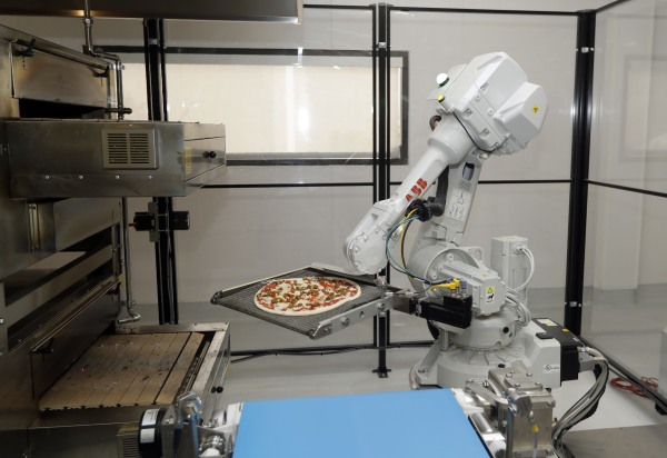 Image: A robot places a pizza into an oven at Zume Pizza