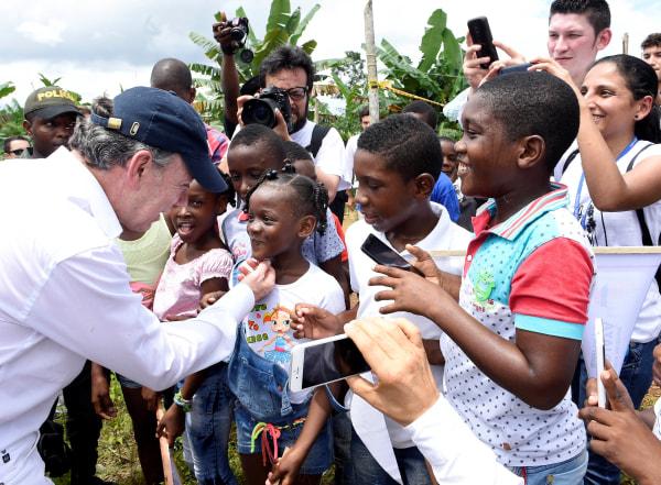 Image: Nobel Peace Prize winner Colombia's President  Juan Manuel Santos greets children after arriving  in the Bojaya area