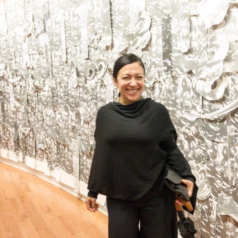 "Artist Scherezade Garcia in front of her piece entitled, ""Sea of Wonder"" in CCCADI's inaugural exhibition, ""Home, Memory, Future."""