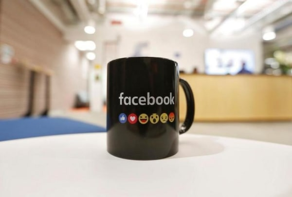 The Facebook logo and emoticons are seen on a coffee mug at the reception of its new office in Mumbai