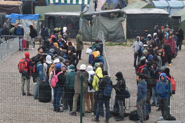 Image: Migrants queue outside a hangar where they will be sorted into groups