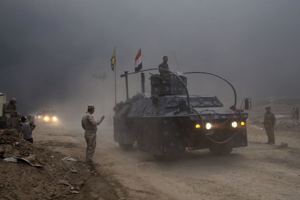 Image: An Iraqi Federal Police vehicle passes through a checkpoint in Qayara