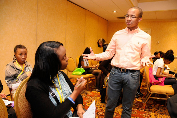 Jaylen Bledsoe, speaks with a conference attendee at the National Society of Black Engineers annual convention in Nashville, TN