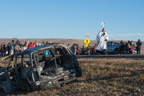 Image: A member of the clergy walks past a burnt out car during a protest of the Dakota Access pipeline on the Standing Rock Indian Reservation near Cannonball