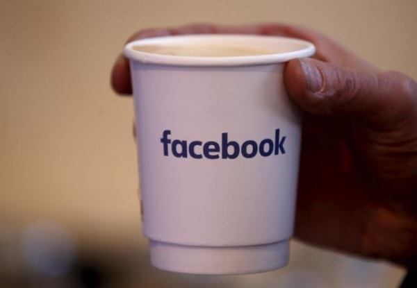 A journalist holds a cups with the Facebook logo at the new Facebook Innovation Hub during a preview media tour in Berlin