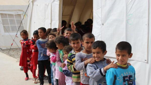 Image: Iraqi school children form a line outside their makeshift classroom