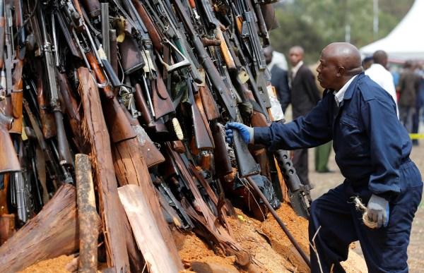 Image: A worker arranges an assortment of guns during a public destruction of 5250 illicit firearms