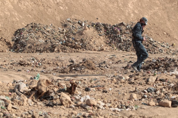 Image: A member of the Iraqi forces check a mass grave they discovered in the Hamam al-Alil area