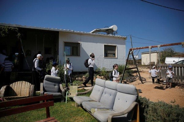 Image: Visitors walk in a yard near a home in the Jewish settler outpost of Amona