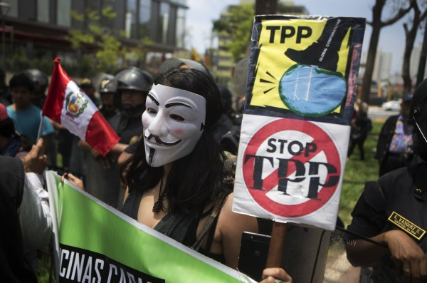 Image: A protester holds signs against the Trans Pacific Partnership (TPP) during a rally in Lima