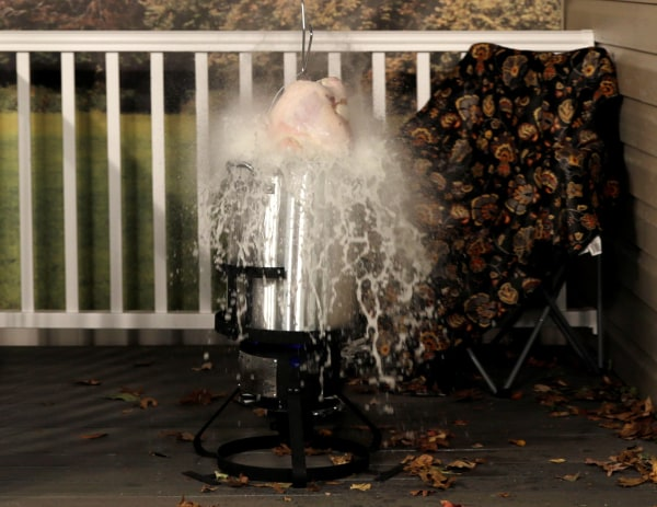 Image: Frozen turkey is dropped into a deep fryer at a food safety demonstration in Rockville
