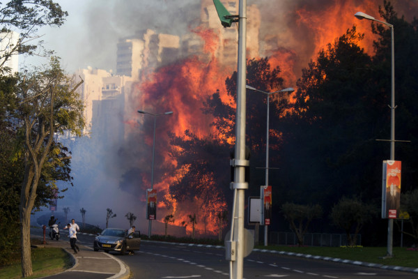 Image: People run as wildfires rages in Haifa, Israel