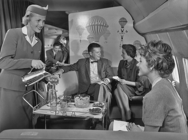 Image: A flight attendant serves cocktails in the lounge of a new Pan American World Airways (Pan Am) Boeing 707, circa 1958.