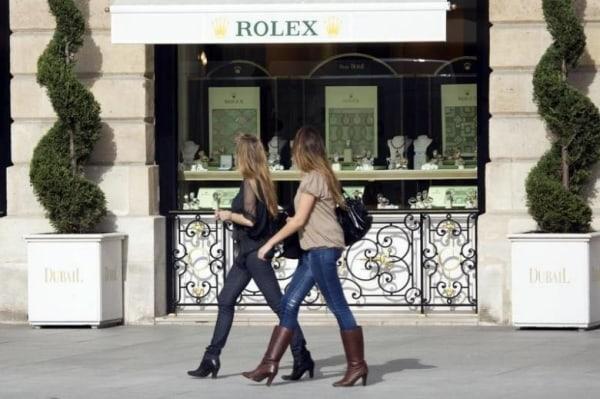 Women walk past a window display of luxury goods maker Rolex in Paris' Place Vendome