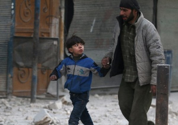 Image: A man holds the hand of a boy