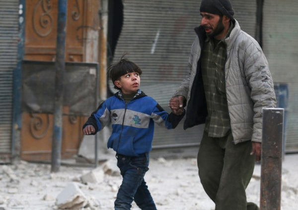 Image: A man holds the hand of a boy as they flee deeper into the remaining rebel-held areas of Aleppo