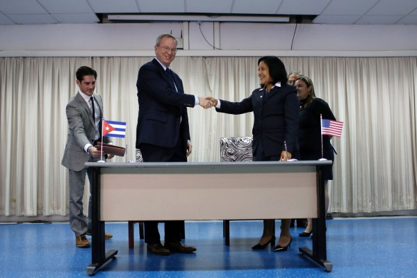 Eric Schmidt, chairman of Alphabet Inc. (L) and Mayra Arevich Marin, president of state telecommunications monopoly ETECSA, shake hands after signing documents in Havana, Cuba