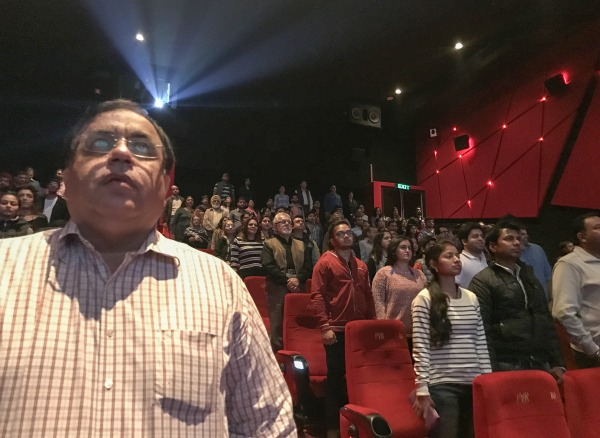 Image: Indian movie goers stand up as national anthem is played at a movie hall before the screening of a movie in Jammu