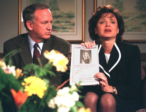 Image: John Ramsey looks on as his wife Patricia holds up