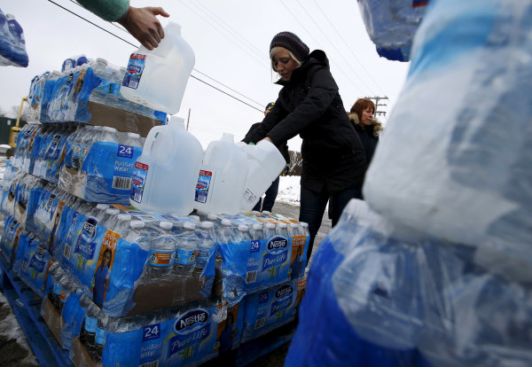 Image: Volunteers distribute bottled water to help combat the effects of the crisis when the city's drinking water became contaminated with dangerously high levels of lead in Flint