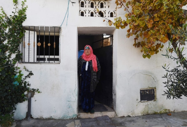 Image: The mother of 24-year-old Anis Amri stands outside her home