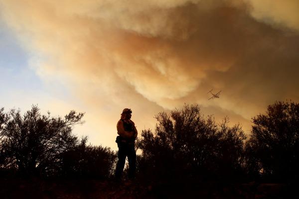 Image: A fire captain watches a fire's movement as an aircraft flies overhead during the Pilot Fire near in San Bernardino, California