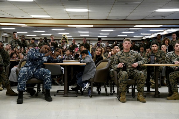 Image: U.S. military personnel and their families listen as U.S. President Barack Obama and First Lady Michelle Obama speak on Christmas day at Marine Corps Base Hawaii in Kailua