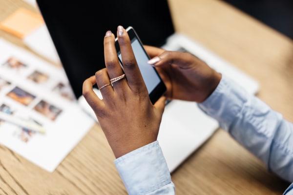 Hands of black businesswoman using smart phone