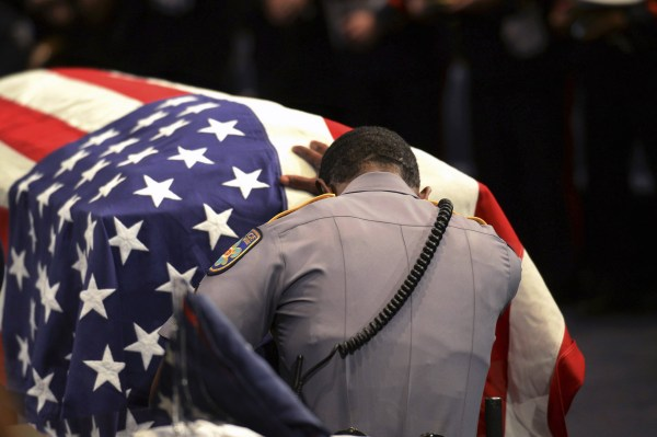 Image: A member of Baton Rouge police Cpl. Montrell Jackson's unit kneels and touches his casket