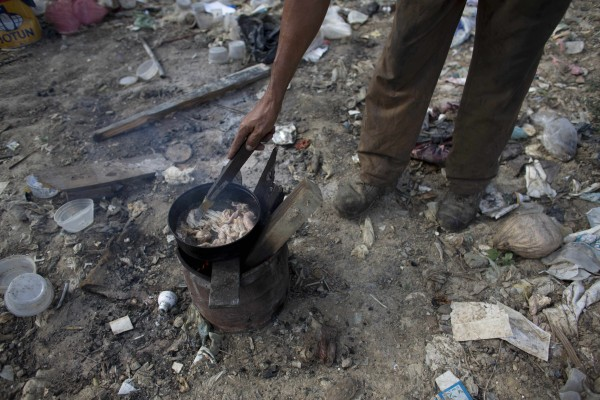 In this Nov. 1, 2016 photo, a man cooks chicken skin he found at the dump in Puerto Cabello, Venezuela, the port city where the majority of Venezuela's imported food arrives.