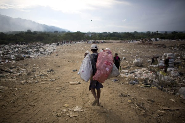 Image:In this Nov. 1, 2016 photo, a man carries bags of recyclable material he collected at the dump in Puerto Cabello, Venezuela.