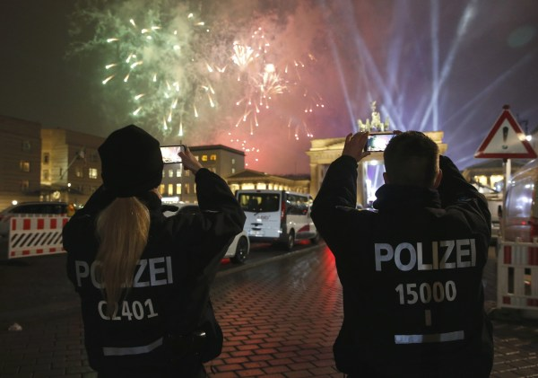 Image: German police officers take pictures as fireworks explode next to the Quadriga sculpture atop the Brandenburg gate during New Year celebrations in Berlin
